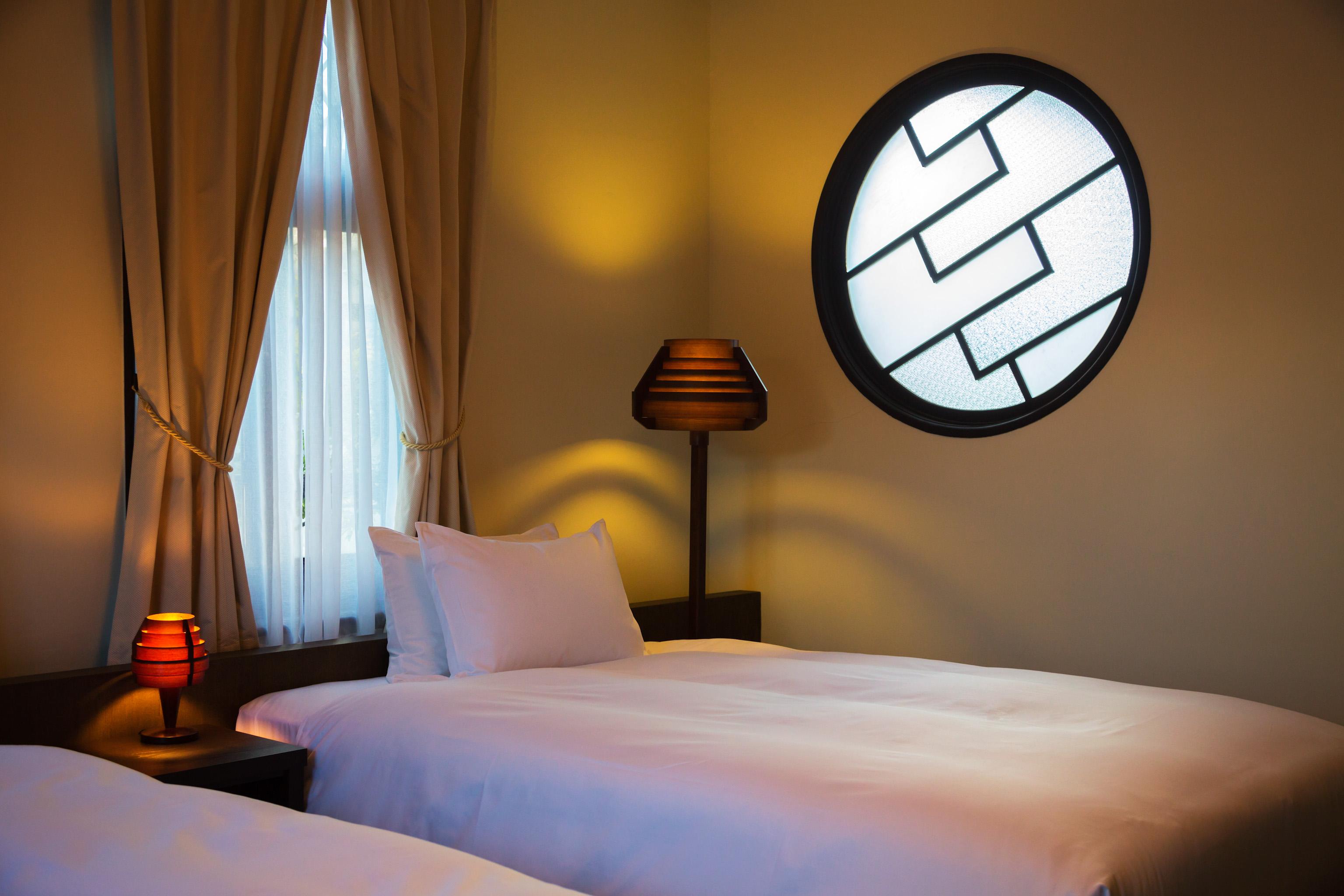 丸窓が印象的な島居邸洋館「望」のベッドルーム。